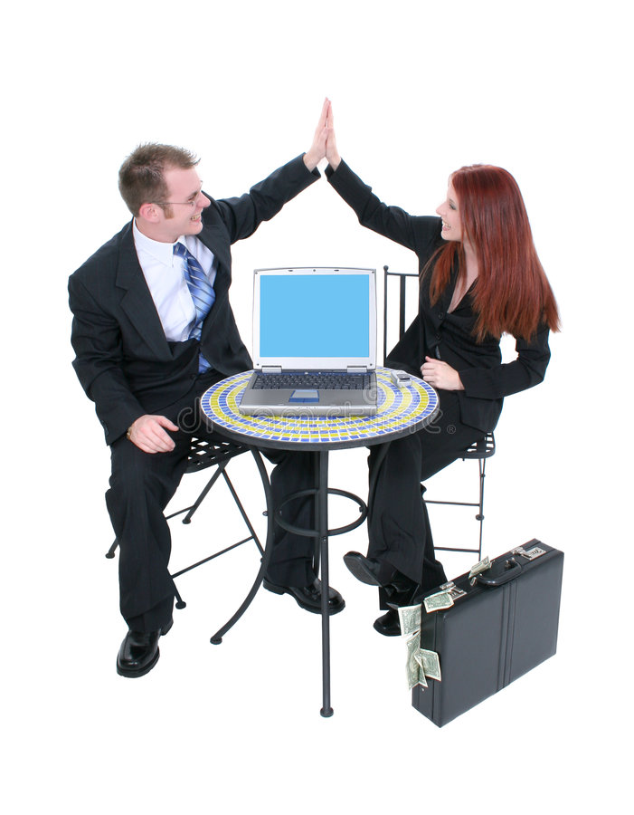 Business Team High Five. Attractive business team at bistro table giving high five. Laptop screen facing camera. Briefcase of money on floor. Shot in studio over stock photos