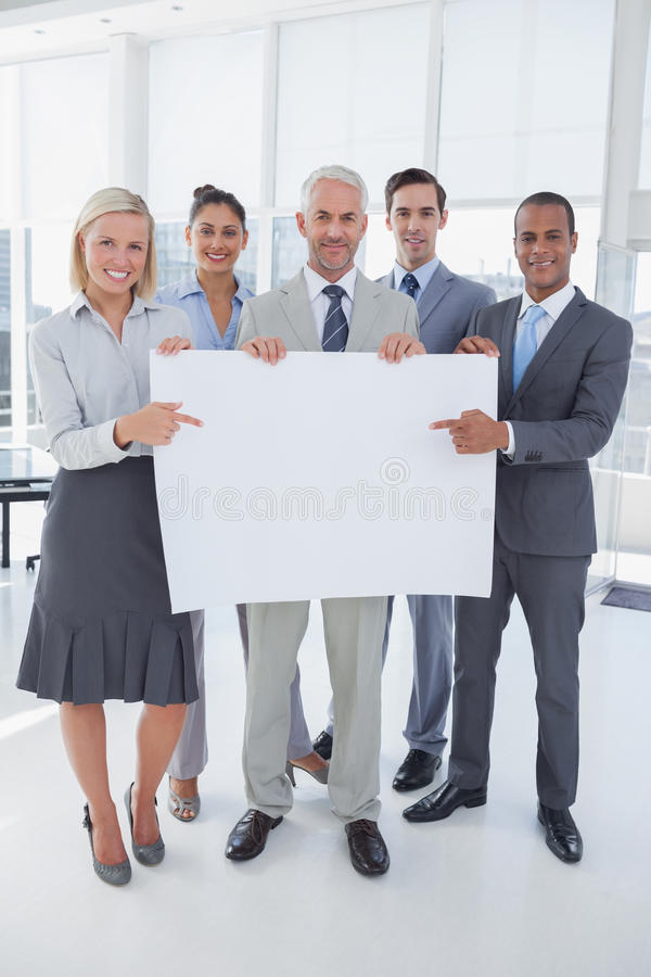 Business team holding large blank poster and smiling at camera. In bright office stock photography