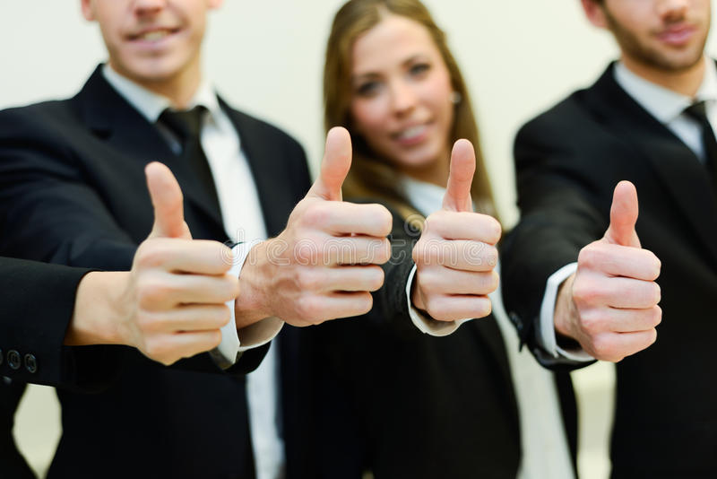 Business team holding their thumbs up royalty free stock images