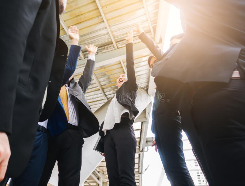 Business team joining hands together standing Hand Raised successful and congrats concept. stock photography
