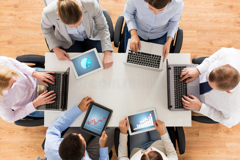 Business team with laptop and tablet pc. Business, people and technology concept - close up of creative team with laptop and tablet pc computers displaying stock photo