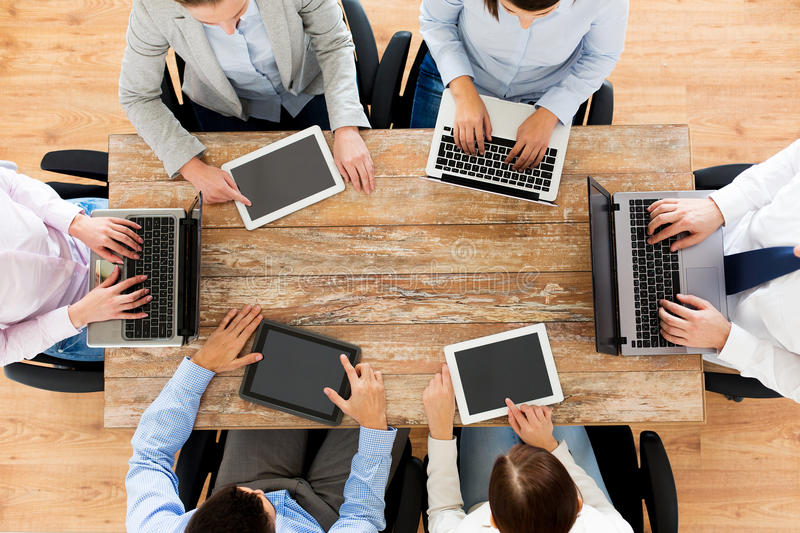 Business team with laptop and tablet pc. Business, people and technology concept - close up of creative team with laptop and tablet pc sitting at table in office stock photography