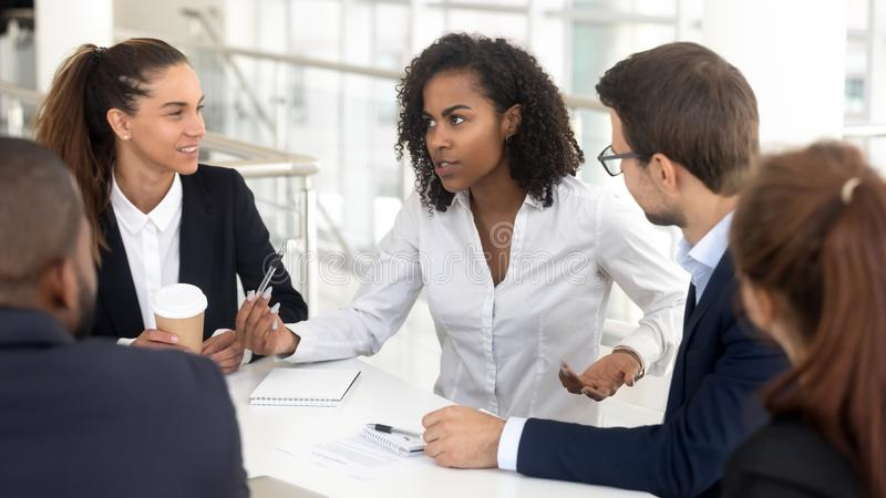 Business team listen to african businesswoman coach speaking at training. Business team listening to african businesswoman coach speaking at training explaining royalty free stock photos
