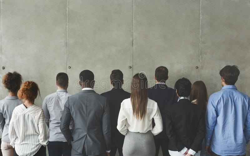Business team looking at grey wall with empty space royalty free stock image