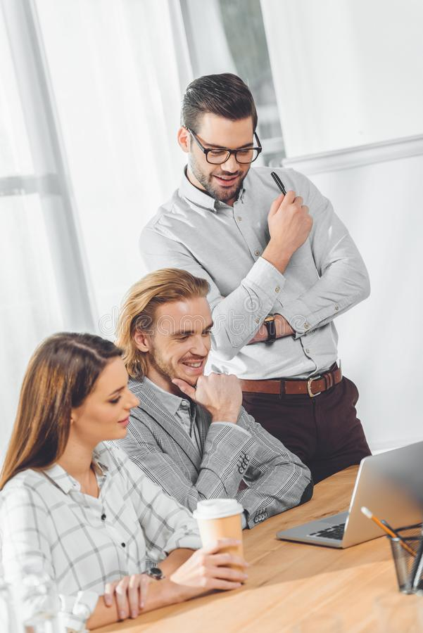 business team looking on laptop on table at office royalty free stock images