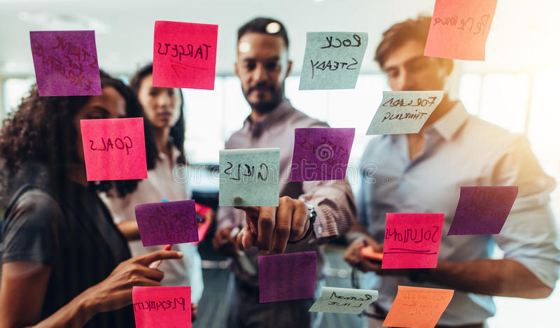 Business team looking at sticky notes posted on glass wall in o royalty free stock image