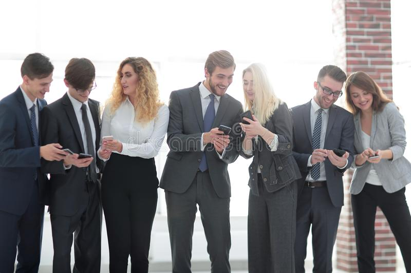 Business team looking to smartphone in office stock image