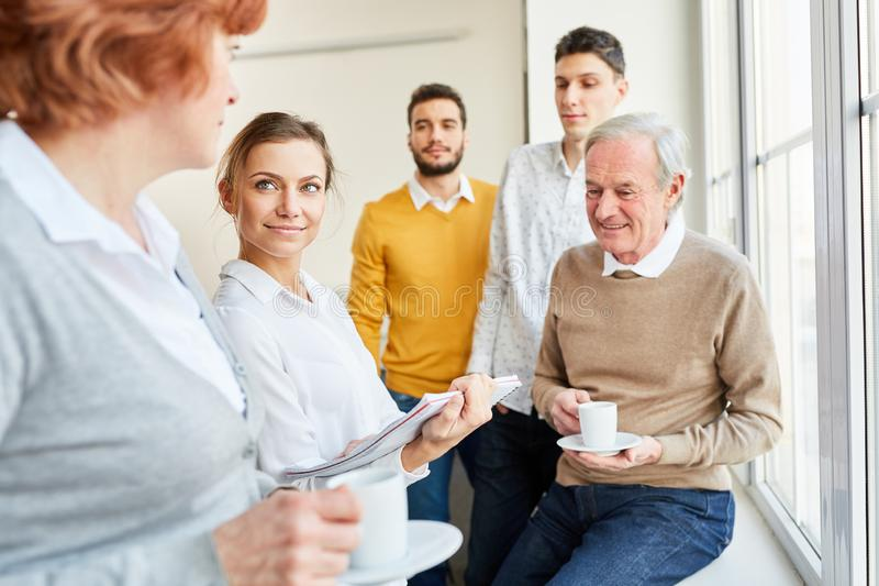 Business team making small talk. With students in coffe break stock image