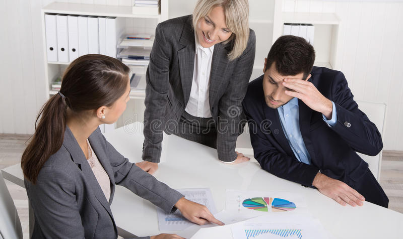 Business team of man and woman sitting around a table talking to. Business team of men and women sitting around a table talking together in a meeting stock photography