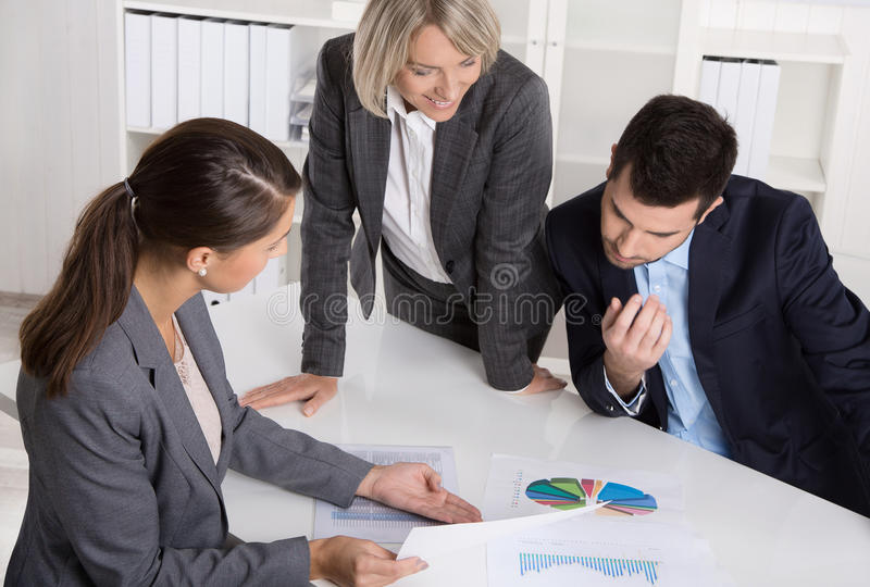 Business team of man and woman sitting around a table talking to. Business team of men and women sitting around a table talking together in a meeting stock image
