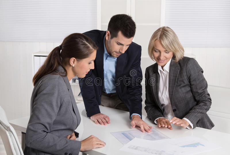 Business team of man and woman sitting around a table talking to. Business team of men and women sitting around a table talking together in a meeting stock photo