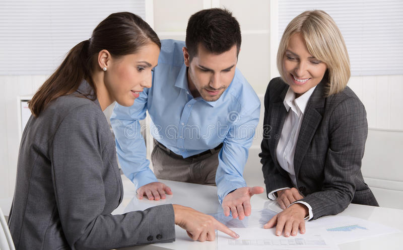 Business team of man and woman sitting around a table talking to. Business team of men and women sitting around a table talking together in a meeting royalty free stock image