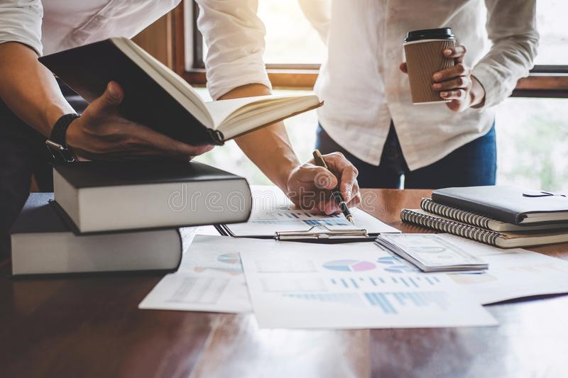 Business team are meeting and discussing marketing plan and pointing graph report analyzing financial figures denoting. The progress in the work royalty free stock photo