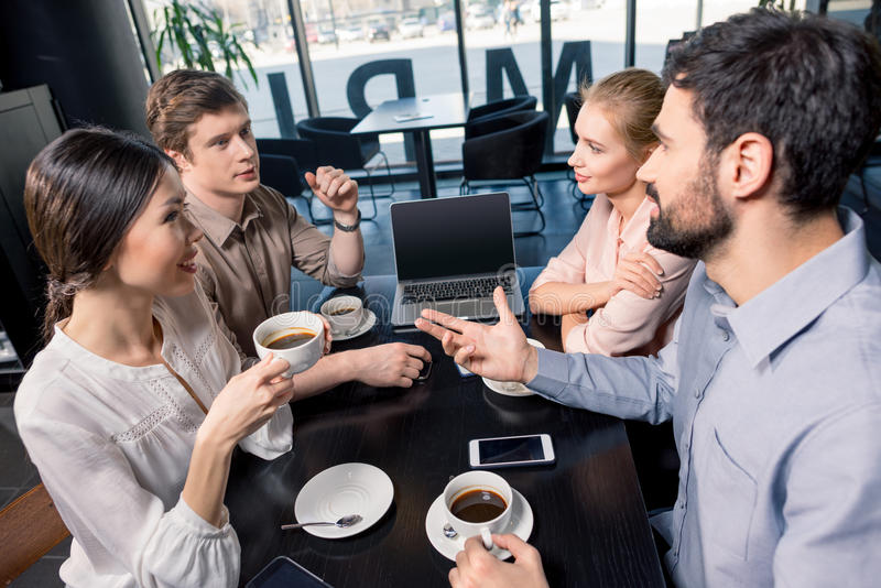 Business team on meeting discussing project with laptop in cafe royalty free stock photography