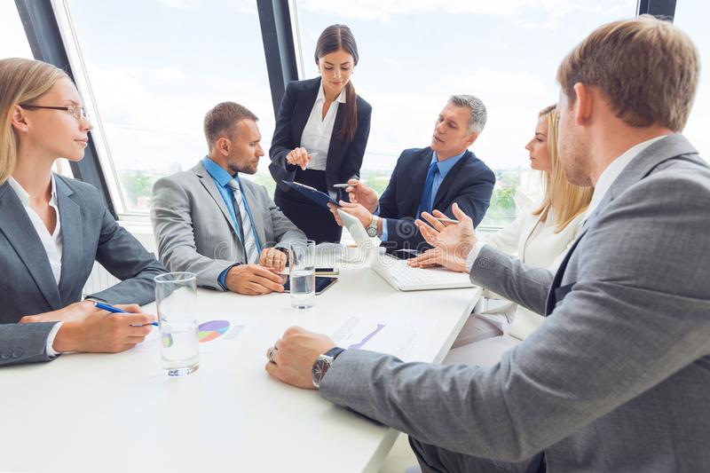 Business team meeting. People in office working with laptop computer and financial reports in desk royalty free stock photo