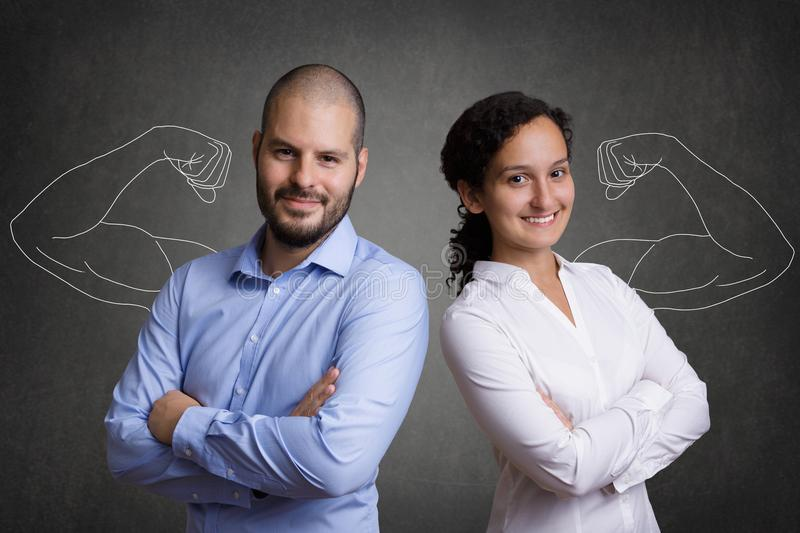 Business Team with muscular arms standing in front of a grey blackboard background royalty free stock photography