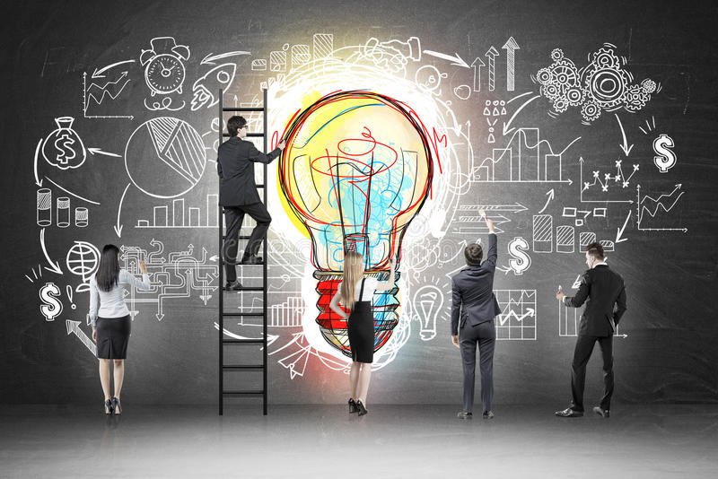 Business team near blackboard with startup sketch. Rear view of business team near blackboard with colorful light bulb and startup sketch drawn on it. Concept of royalty free stock photography