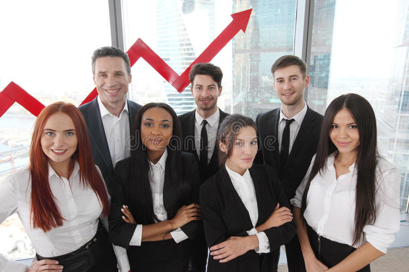 Business Team. Portrait of business team of men and women in office with arrow graph of income growth stock photo