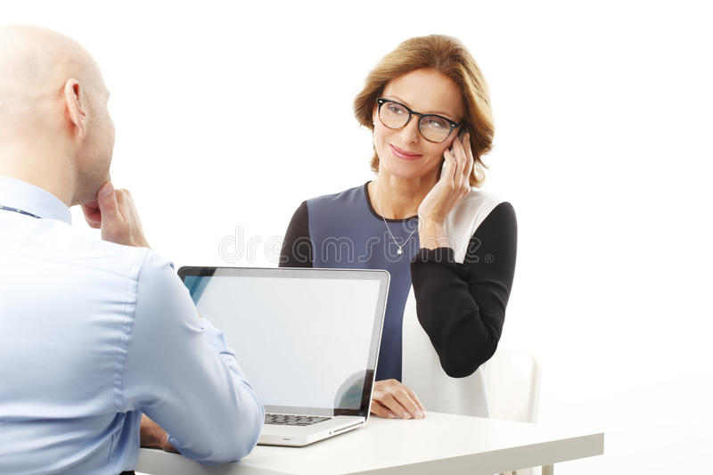 Business team. Portrait of business team sitting at desk while businessman using laptop and busy business women giving advise by phone. Isolated on white royalty free stock image