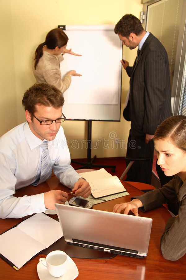 Business Team Preparing a Prop. A business team of two men and two women, work on putting together a business proposal for a client royalty free stock photography
