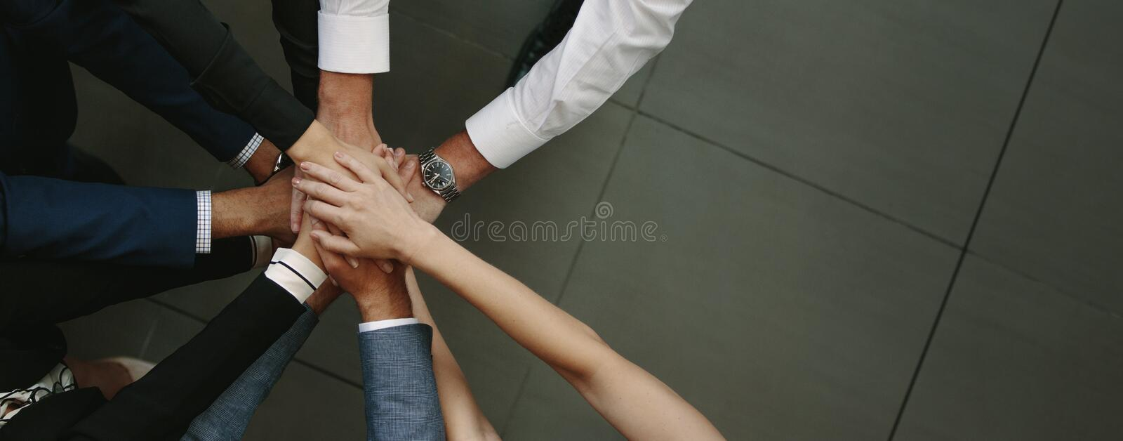 Business team putting hands together. Overhead view of business team putting hands together at the office. Office workers making a stack of hands with copy space stock photos