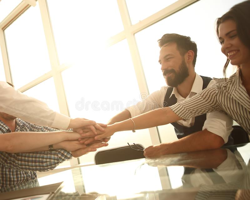 Business team putting their hands together over the Desk stock image