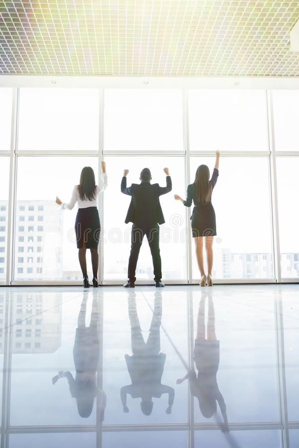 Business team raised hands in office satisfied with result, won profitable contract, group of winners celebrate victory or great s stock photo