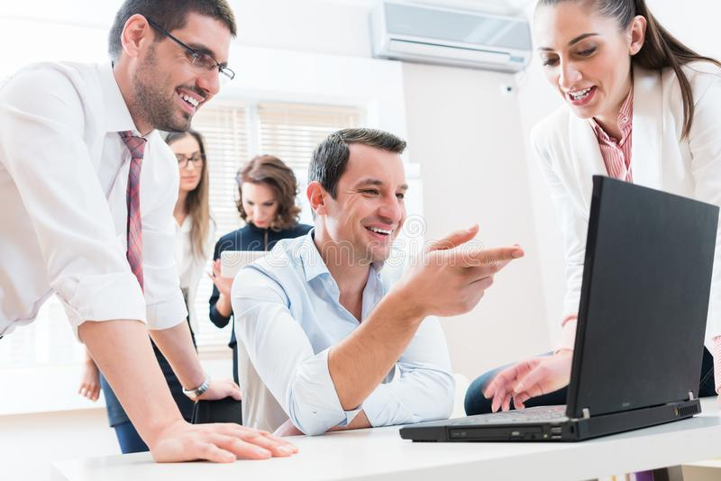Business team reporting to boss having meeting in office. Discussing report on computer royalty free stock photography
