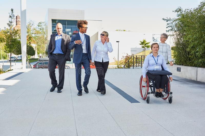 Business team on the road with colleague in a wheelchair. Business people from the multicultural business team with a colleague in a wheelchair royalty free stock photos