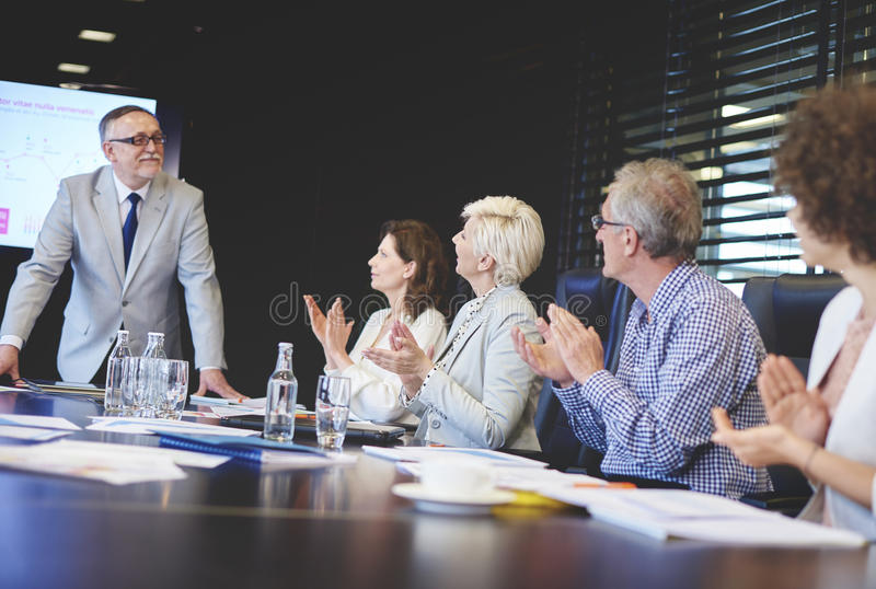 Business team. Senior adults business admiring male public speaker stock photography