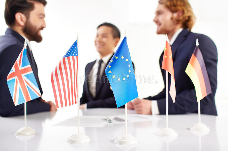 Business team. Several flags on negotiation table, three business people discussing in the background stock image