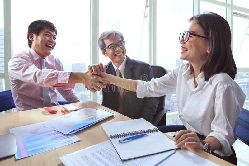Business team shaking hand and laughing happiness for successful stock images