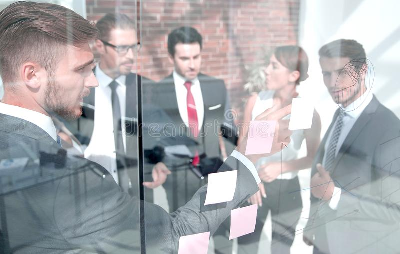 Business team showing on the notes on the glass Board royalty free stock photography