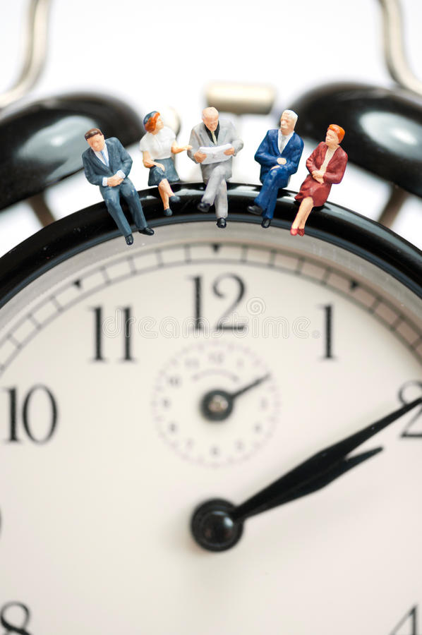 Business team sitting on top of the giant clock royalty free stock photography