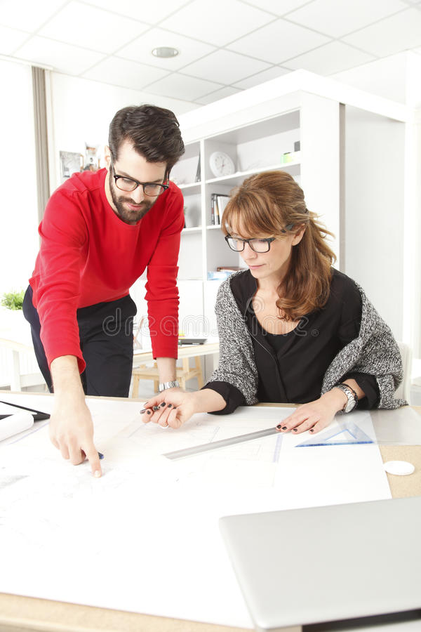Business team in small architect studio. Business women and businessman working together in small architect studio royalty free stock image