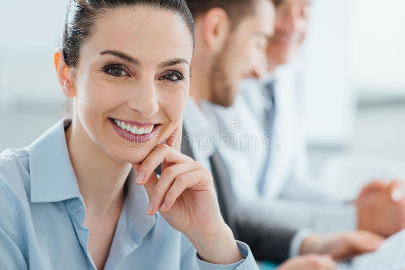 Business team and smiling businesswoman posing stock image