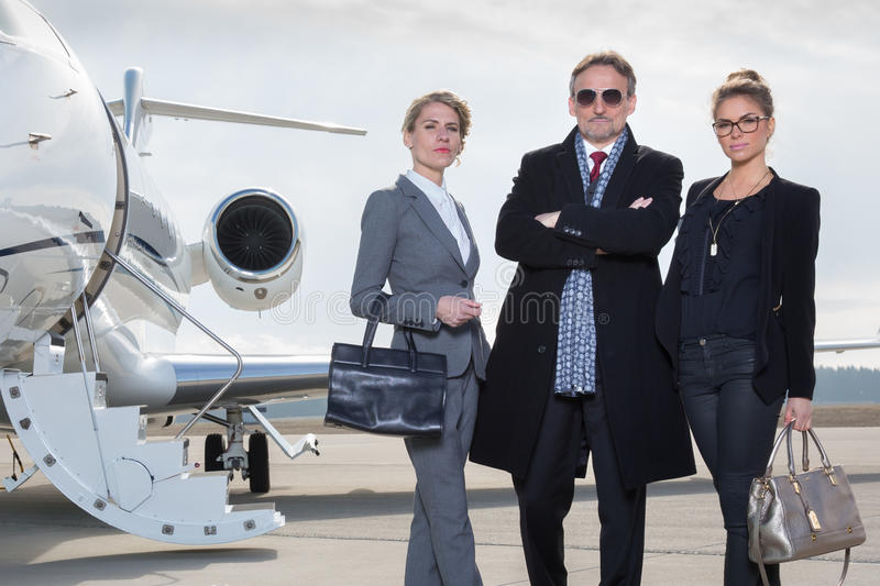 Business team standing in front of private jet. And looking to camera royalty free stock images