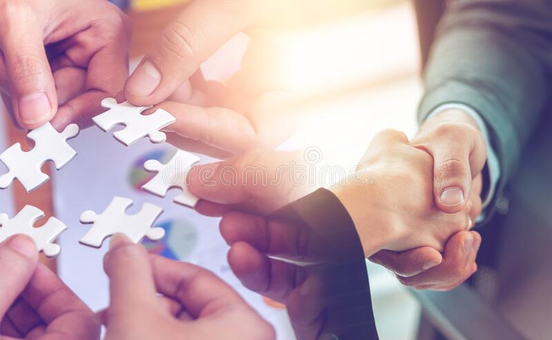 Business team strategy concept with jigsaw handshaking for business team solution success concept stock photo