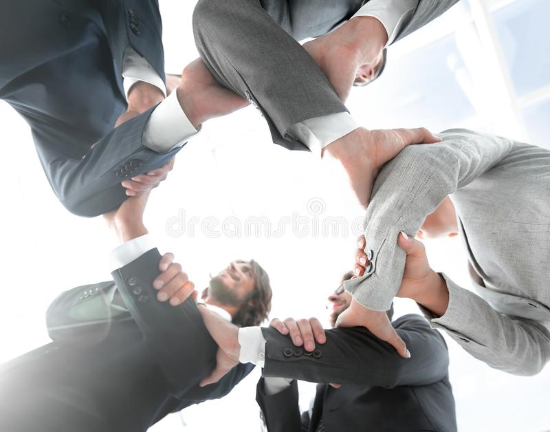 Business team are taking each other`s hands. Bottom view.the business team are taking each other`s hands.the concept of teamwork royalty free stock photo
