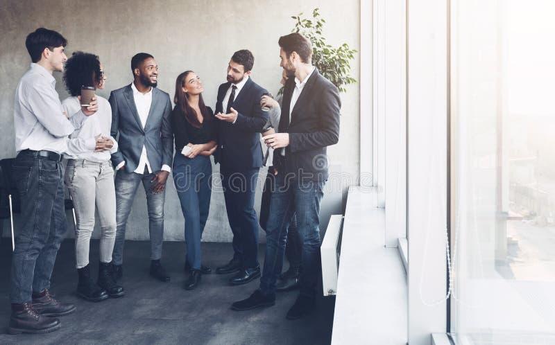 Business team talking at coffee break near window royalty free stock image