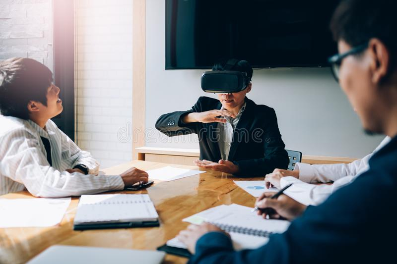 Business team testing virtual reality VR headset technology with colleague in office stock photos