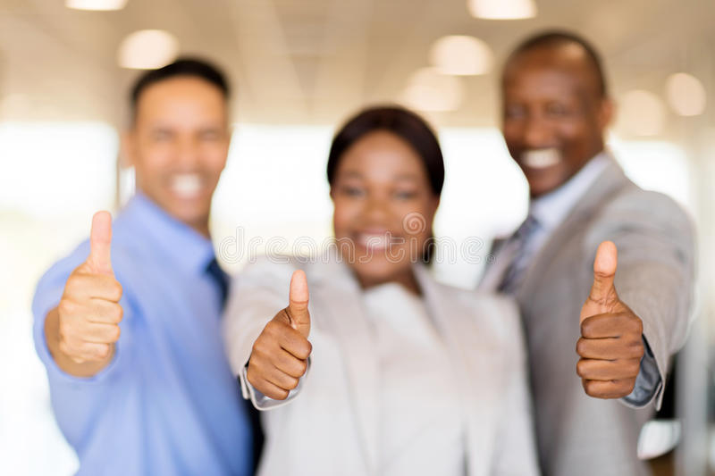 Business team thumbs up. Closeup portrait of business team giving thumbs up stock photo