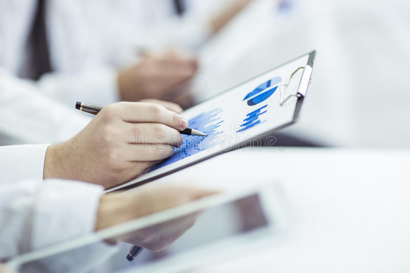 Business team using digital tablet performs analysis of marketing graphics stock photos