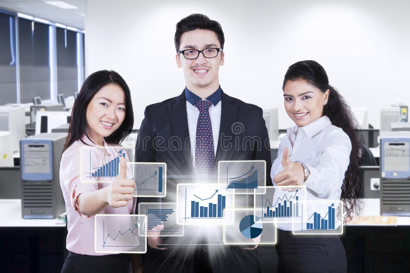 Business team with virtual financial growth in workplace. Group of young business people showing virtual financial growth on the laptop and thumbs up while stock photography
