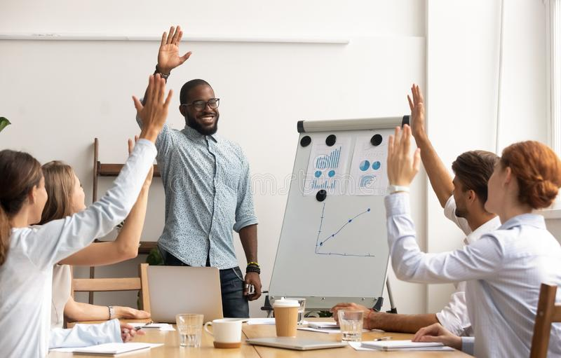 Business team voting concept, african coach and employees raise hands. Business team voting concept, smiling african coach leader and diverse employees group stock images