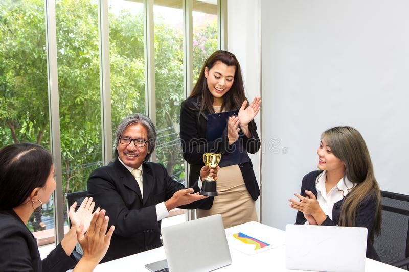 Business team winning trophy in the office . Businessman with teamwork in award and successful showing trophy and rewarded for in royalty free stock photos