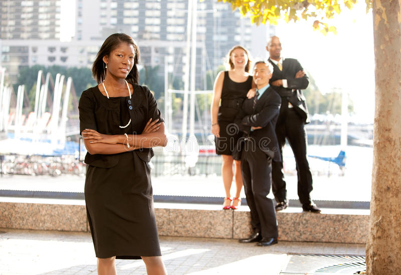 Business Team Woman. An African American woman in front of a business team royalty free stock photography