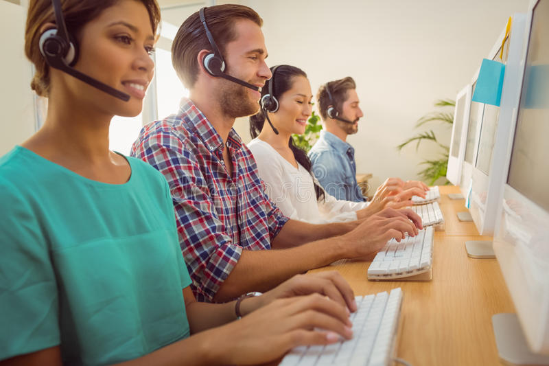 Business team working at the call centre. Business team working together at a call centre wearing headsets royalty free stock images