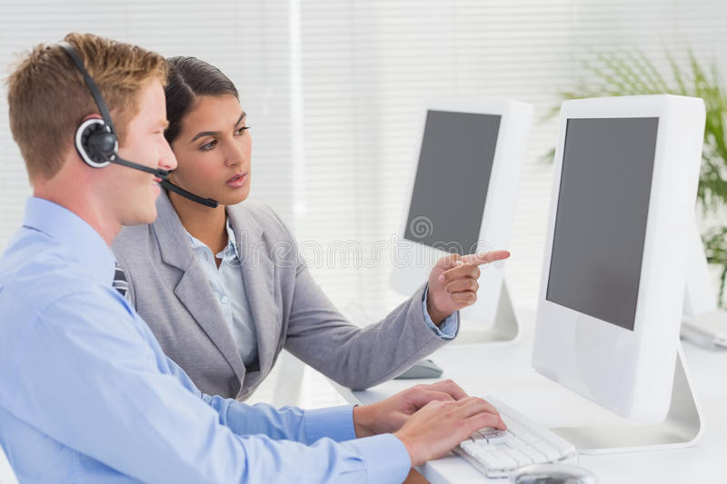 Business team working on computers and wearing headsets royalty free stock image