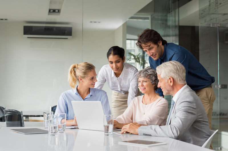 Business team working. Business people having meeting around table in modern office. Group of businessmen and businesswomen working together on computer during a stock image